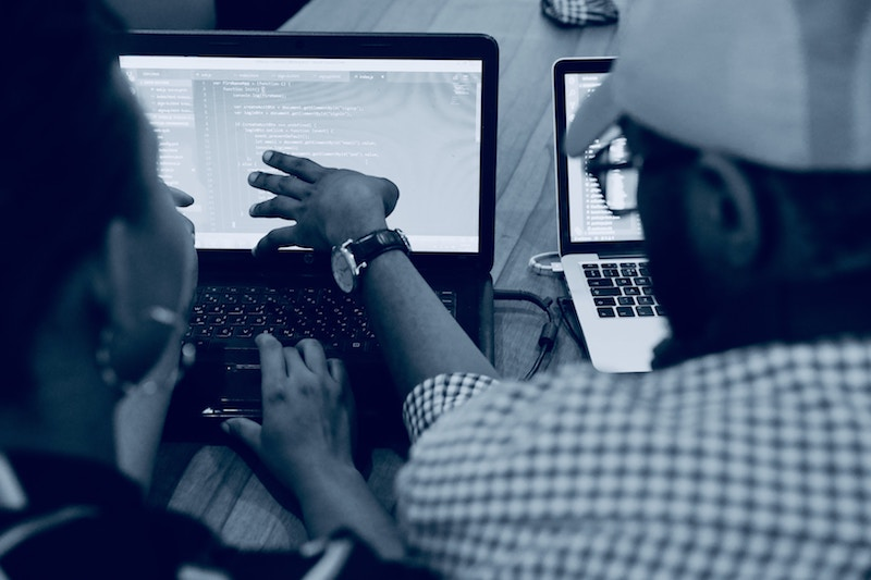 coding on a computer two people one pointing to screen
